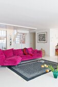 White and grey patterned rug in front of magenta couch in bright living room