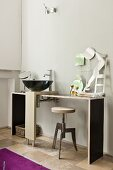 Black designer sink on MDF washstand and welded swivel stool in minimalist interior