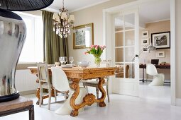 Various chairs around solid wooden dining table with carved base in traditional dining room with view into study through open double doors