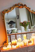 Lit, white pillar candles in front of mirror with antique gilt frame reflecting vase of tulips on coffee table