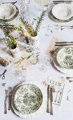 Gedeckter Tisch mit Vintage Tellern in Toile de Jouy, in der Mitte brennende Kerze und Vasen mit Kräutern
