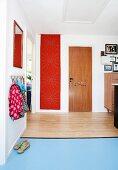 Gangbereich mit Kindergarderobe, verschiedene Beläge, Holz und hellblauer Linoleum auf Boden, im Hintergrund rote Fahne mit Lochmuster an Wand