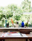 Tisch mit Malutensilien und Zeichnung vor Fenster mit Aussicht, auf Fensterbank Vasen und Behälter mit Stiften
