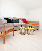 Baumstämme als Beistelltisch vor naturfarbenem Sofa in minimalistischer Wohnzimmerecke, seitlich Sessel im Fiftiesstil