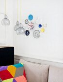 Patchwork scatter cushion below pendant lamps and decorative wall plates on wall