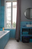 Pale blue bathroom with mosaic tiles, grey-painted walls and vintage ambiance