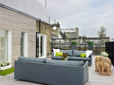 Elegant grey sofas and sandstone elephant ornaments on roof terrace with wooden decking
