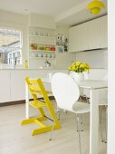White retro shell chair and yellow-painted Tripp Trapp chair in white, modern, fitted kitchen with yellow accents