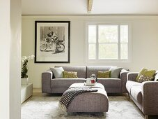 Modern grey sofa set with matching ottoman used as coffee table in traditional living room with black and white photo on wall