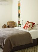Box-spring bed with brown bedspread and patterned scatter cushions next to narrow bookcase in niche in simple bedroom