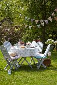 Summer garden party with romantic set table, comfortable garden chairs with seat cushions and vintage-style bunting