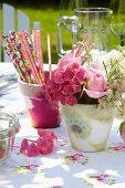 Romantische Tischdekoration mit Serviettentechnik, geblümter Tischdecke und rosafarbenen Sommerblüten