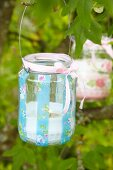 Tealight holder romantically decorated with pink ribbon hanging from branch