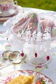Selbstgenähte Fliegenschutzhaube aus weißem Spitzenstoff für Erdbeerschale auf romantisch gedecktem Gartentisch