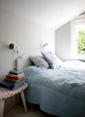 Double bed with white headboard below window and stacked books on stool used as bedside table in bedroom