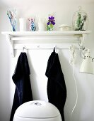 Bathroom utensils on white wall bracket and black towels hung from hooks