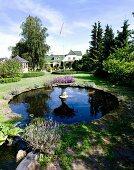 Pflanzengefäss auf Stele aus Stein im Karpfenteich in angelegtem Garten, im Hintergrund Landhaus
