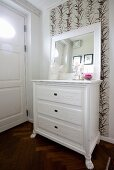 Framed mirror on top of white-painted chest of drawers against leaf-patterned wallpaper