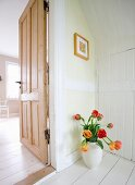 White vase of red and yellow tulips on white-painted wooden floor next to open interior door