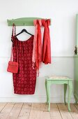 Red dress on coat hanger and scarves hung from green-painted coat rack with matching side table with curved legs