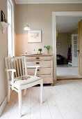 White-painted, rustic armchair on wooden floor in front of chest of drawers next to doorway