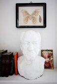 White plaster bust of man on bookshelf below framed buttefly