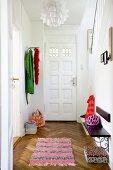 View through open door into hallway with rug, herringbone parquet floor, coat rack and wooden bench mounted on wall