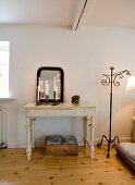 Lit candles in candlesticks in front of mirror on white console table with carved legs; vintage standard lamps with wrought iron frame