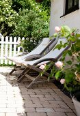 Wooden deckchairs with white seats on terrace outside house with garden in background