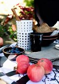 Red apples, bowl of blueberries and crockery on table outdoors