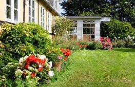 Summery garden with neat lawn and flowering plants outside house with conservatory