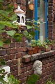 Ceramic tealight holder and head sculpture on old brick wall with blue window frames and potted geraniums on windowsill