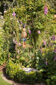 Pink foxgloves and garden ornaments in idyllic garden