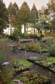 Herbstliche Beete mit Stauden und Grünpflanzen, Gartenregal mit Tontöpfen und Baumgruppe im idyllischen Hintergrund