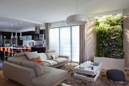 Corner sofa, coffee table and vertical wall planter in lounge and open-plan kitchen with orange bar stools in background