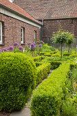 Formhecken halbhoch und Buchsbüsche im Garten vor Bauernhaus aus Ziegel