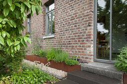 Stufen vor Glastür eines Ziegelhauses, davor Hochbeet mit rostiger Metalleinfassung