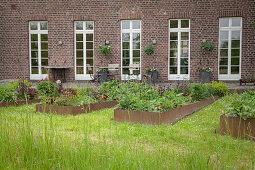 Hochbeete mit Metalleinfassung vor renoviertem Bauernhaus aus Ziegel