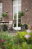 Blick vom Garten auf Sitzplatz, Klappstühle und Tisch vor Bauernhaus aus Ziegel, weisse Sprossentüren
