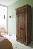 Board doors with iron hinge straps on rustic wardrobe against lime green wall