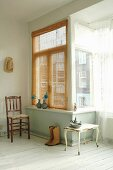 Old chair, side table, cowboy boots and pewter ornaments arranged next to window bay