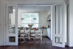 Essplatz im Landhausstil mit Antikstühlen an langer Tafel in einer modernen, weissen Wohnküche