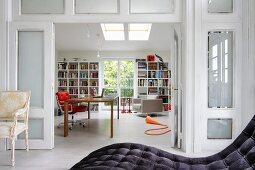 Blick durch geöffnete Faltglastüren ins Arbeitszimmer mit Bücherregal, Schreibtisch und rotem Drehstuhl, Antikstuhl und moderne Tagesliege im Vordergrund