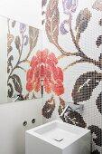 Blumenmosaik - seitlich in Spiegel reflektiert - hinter modernem, kubischem Waschbecken mit Designer-Wandarmatur