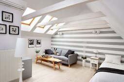 Bright interior with exposed roof structure, grey sofa against grey and white striped back wall and pale wooden table