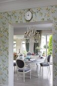 Dining area with opulent chandelier above antique-style white dining table and chairs