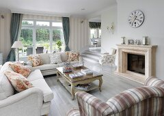 Pale sofa set in front of fireplace in traditional interior; steps leading to raised dining area in background