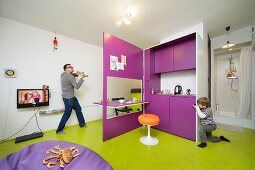 Father and son playing in multifunctional room with creative modular kitchen, beanbag in front of flatscreen TV and shower cubicle in background
