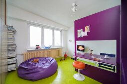 Retro stool at folding table in purple, modular kitchen and beanbag on wooden floor painted lime green