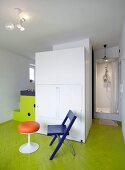Retro stool and folding chair in front of closed modular kitchen on lime green parquet floor with shower cubicle in background